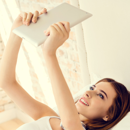 Young happy smiling woman using no-name tablet computer, at home