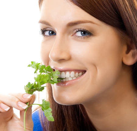 Cheerful woman eating potherbs, isolated over white background