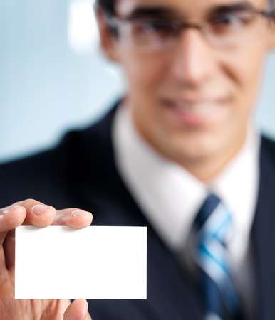 businesscard: Happy smiling businessman showing blank business card, at office. Focus on hand.