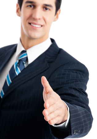 Happy smiling young business man giving hand for handshake, isolated over white background. Focus on hand. Stock Photo