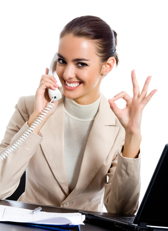 Business woman with phone showing thumbs up sign, at office, isolated over white background Stock Photo