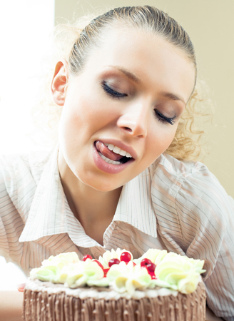 Cheerful blond young woman eating torte, indoors Stock Photo