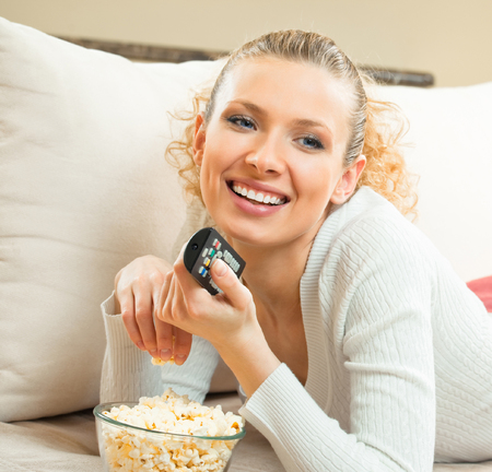 Portrait of young blond happy smiling woman watching TV at home