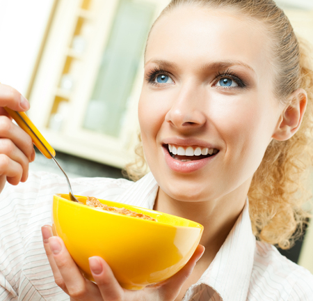 Cheerful blond woman eating cereal muslin Stock Photo