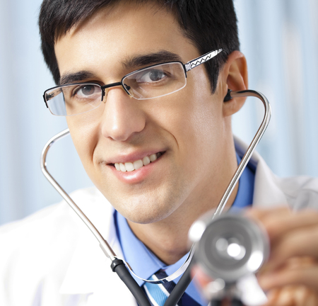 Happy smiling young doctor with stethoscope, at office Stock Photo