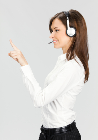 Portrait of happy smiling cheerful customer support phone operator in headset pointing at something, over grey background Stock Photo