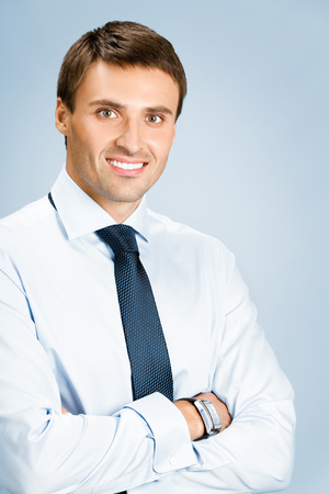 Portrait of happy smiling young business man, over blue background