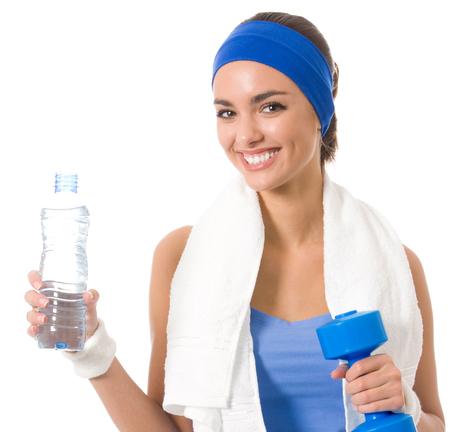 Portrait of cheerful young attractive woman in fitness wear with dumbbell and water, isolated over white background Stock Photo