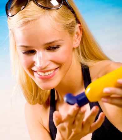 Young beautiful happy smiling cheerful tanned woman with sun-protection cream on beach, during sun bathing Stock Photo