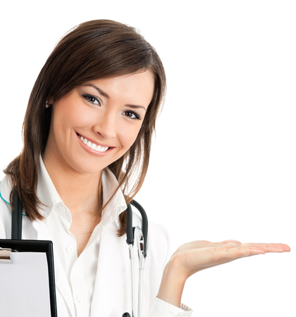Happy smiling young beautiful female doctor showing blank area for sign or copyspace, isolated over white background