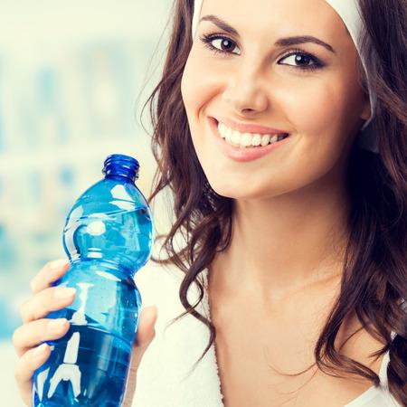 Souriante jeune femme avec une bouteille d'eau, au club de fitness ou de gym, composition carrée Banque d'images