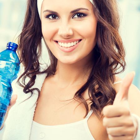 Portrait, de, jeune femme, projection, pouce vers le haut, geste, à, bouteille eau, à, club forme physique, ou, gymnase, composition carrée Banque d'images