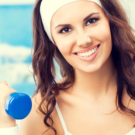 Femme souriante dans les vêtements de fitness exercice avec haltère, au centre de fitness ou de gym, composition carrée Banque d'images