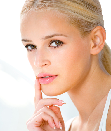 Portrait of beautiful blond woman with finger on lips Stock Photo