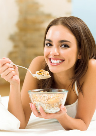 Young woman eating cereal muslin (flakes)