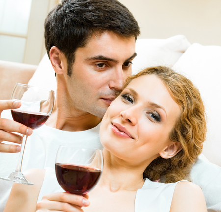 Portrait of cheerful smiling couple with glasses of red wine, indoors