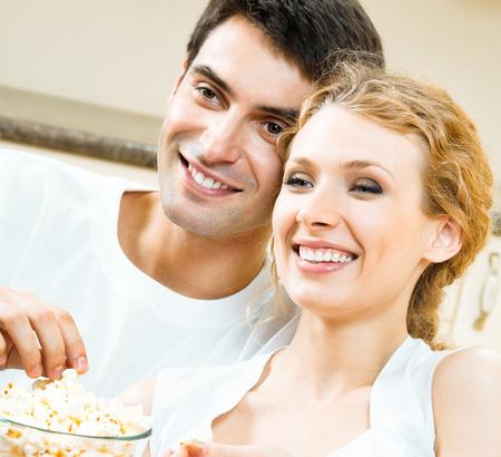 Joyeux jeune couple regardant la télévision ensemble