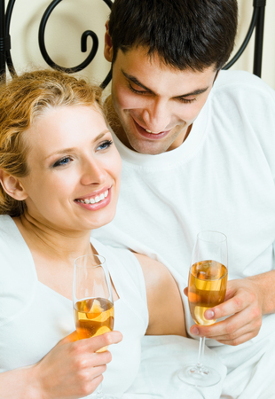 Portrait of cheerful smiling couple with champagne, indoors Banque d'images