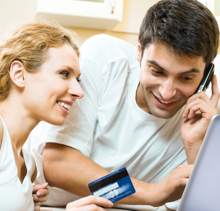 Cheerful smiling couple paying by plastic card with laptop, indoors Banque d'images