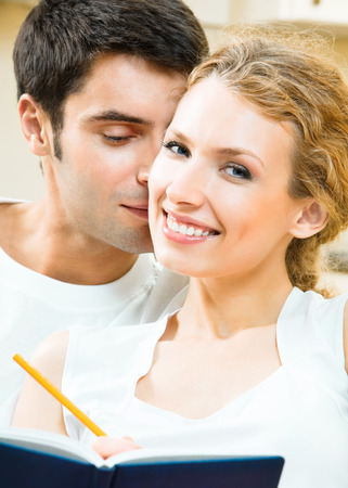 Cheerful smiling young couple with organizer planning, indoors