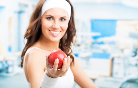 Cheerful woman with red apple, at fitness center or gym, selective focus on hand. Banque d'images