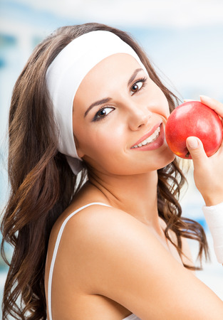Cheerful young beautiful woman with red apple, at fitness center or gym