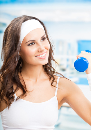 Cheerful woman in fitness wear exercising with dumbbell, at fitness center or gym