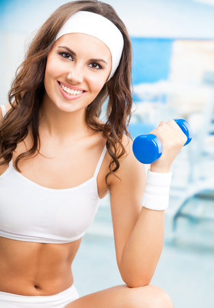 Femme joyeuse en vêtements de conditionnement physique, exercice avec haltères, au centre de fitness ou de gym Banque d'images
