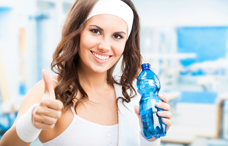 Portrait of cheerful young attractive woman showing thumbs up gesture, with bottle of water, at fitness club or gym