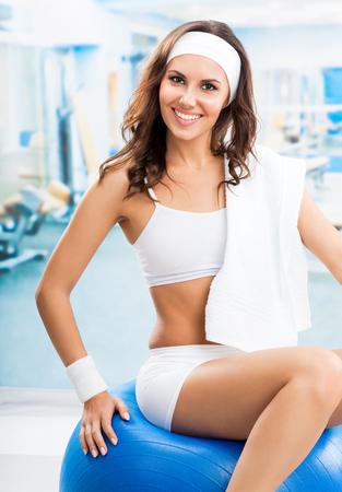 Jeune femme souriante joyeuse, exerçant avec fitball au club de fitness ou à la salle de sport