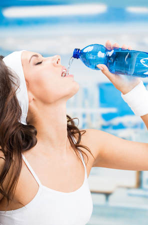 Portrait of cheerful young attractive woman drinking water, at fitness club or gym