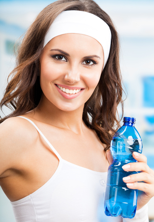 Portrait of cheerful young attractive woman with bottle of water, at fitness club or gym Banque d'images