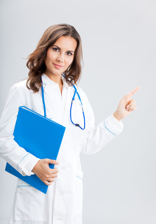 Portrait of young female doctor showing something or copyspase for product or sign text, with blue foder, over grey background