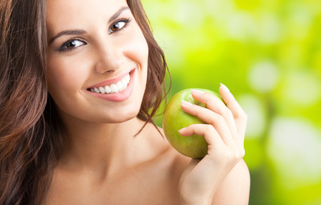 Young happy smiling woman with apple, outdoors, with copyspace for text or slogan