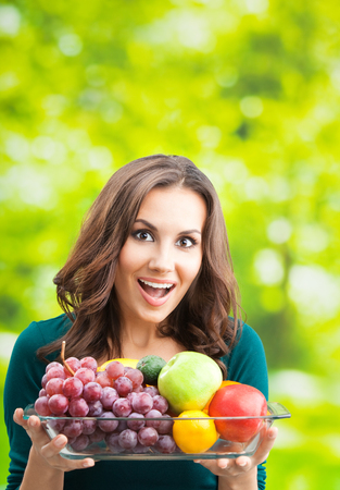 Young happy smiling woman with plate of fruits, outdoors, with copyspace for text or slogan. Banque d'images