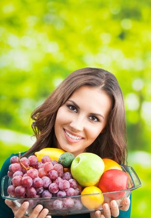Jeune femme souriante heureuse avec assiette de fruits, à l'extérieur, avec fond pour le texte ou le slogan. Banque d'images