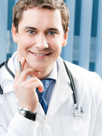Happy smiling young doctor at office Stock Photo
