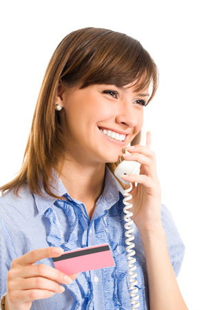 Young happy smiling business woman with plastic card, on cellphone, isolated on white background