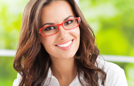 Portrait of young happy smiling cheerful business woman in glasses, at office