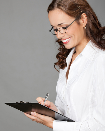 Happy smiling young beautiful business woman with clipboard writing, over gray background Stock Photo