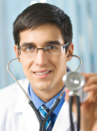 Happy smiling young doctor with stethoscope, at office Banque d'images