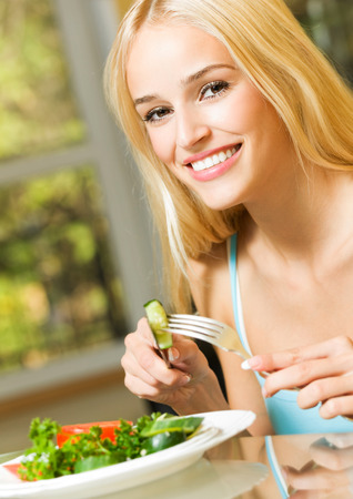 Portrait of happy smiling beautiful blond woman eating salad