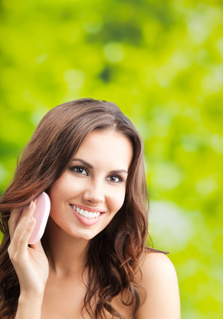 Portrait of happy smiling beautiful young woman cleaning skin by cotton pad, outdoor, with copyspace Banque d'images