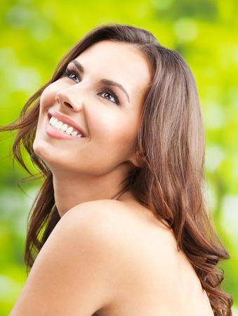 Portrait de la belle jeune femme souriante heureuse avec de longs cheveux, à l'extérieur