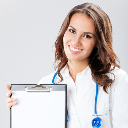 Happy smiling young female doctor showing blank clipboard with copyspace, over grey background