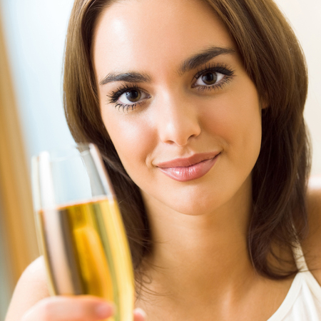 Portrait of young happy smiling woman with glass of champagne, at home
