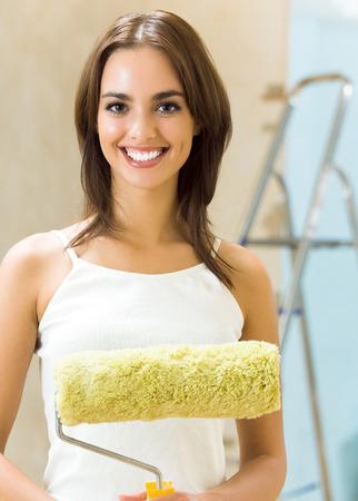 Portrait de jeune femme heureuse avec rouleau à peinture dans la nouvelle maison