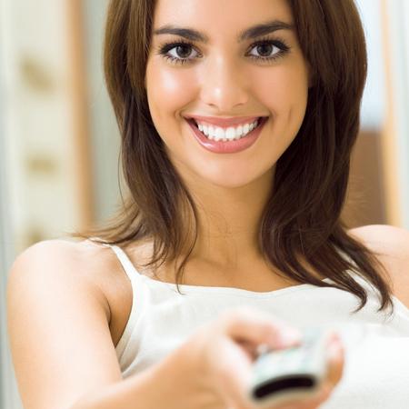 Portrait de jeune femme heureuse sourire en regardant la télévision à la maison Banque d'images