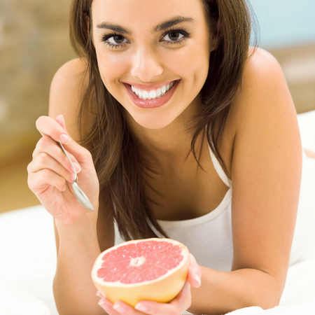 Portarit of young woman eating grapefruit at home Banque d'images