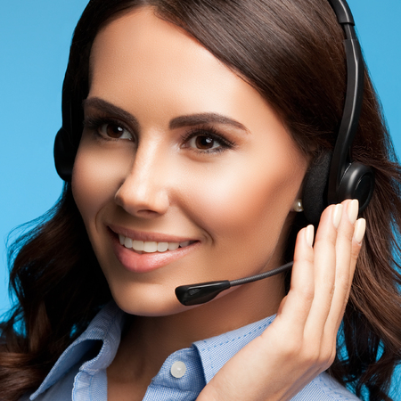 Portrait of attractive customer support female phone operator in headset, on blue background. Consulting and assistance service call center. Stock Photo